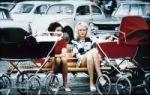 Zwei Frauen mit Kinderwagen auf Parkbank